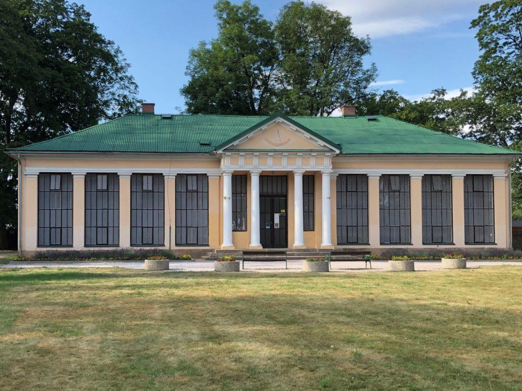 Památník Karla Václava Raise. Světlá budova s antickými sloupy, velkými okny a zelenou střechou uprostřed parku