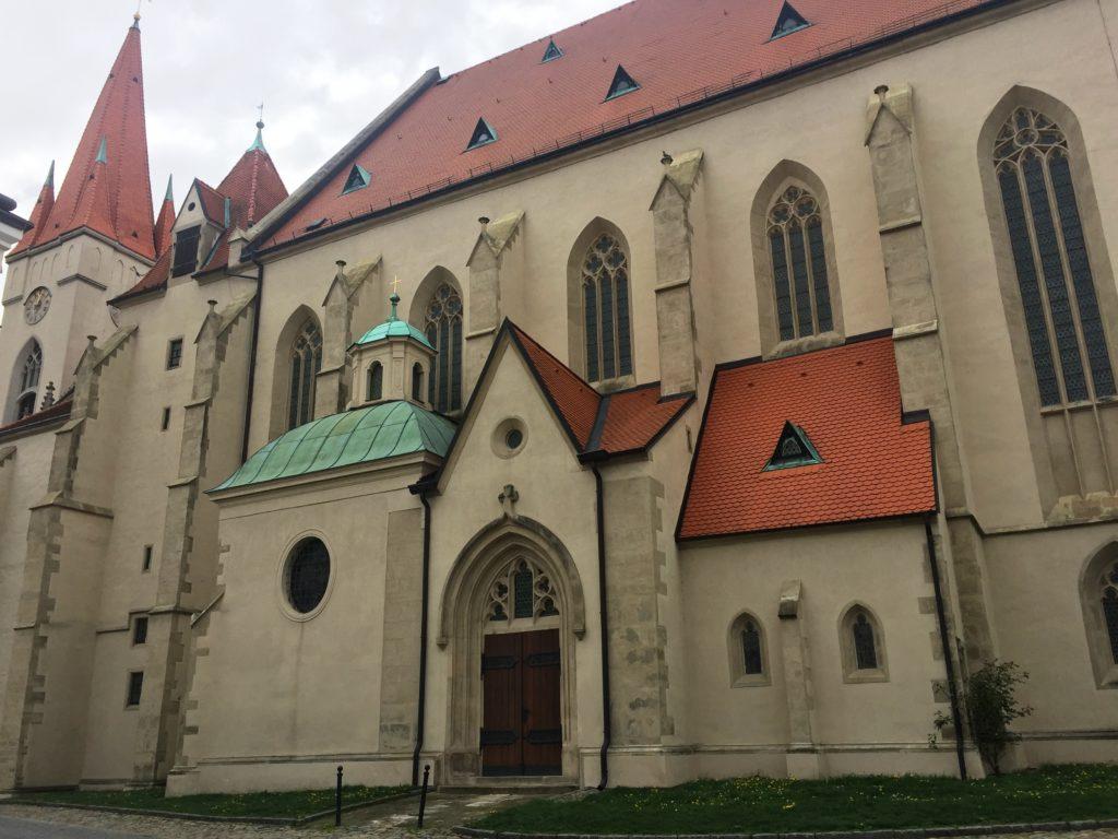kostel svatého Mikuláše ve Znojmě, světlý kostel s červenou střechou a věží, vstupní portál