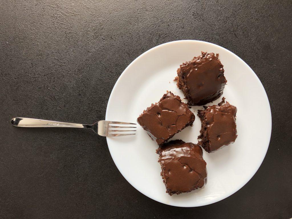 cuketové brownies s čokoládovou polevou na bílém talíři s vidličkou na černém pozadí