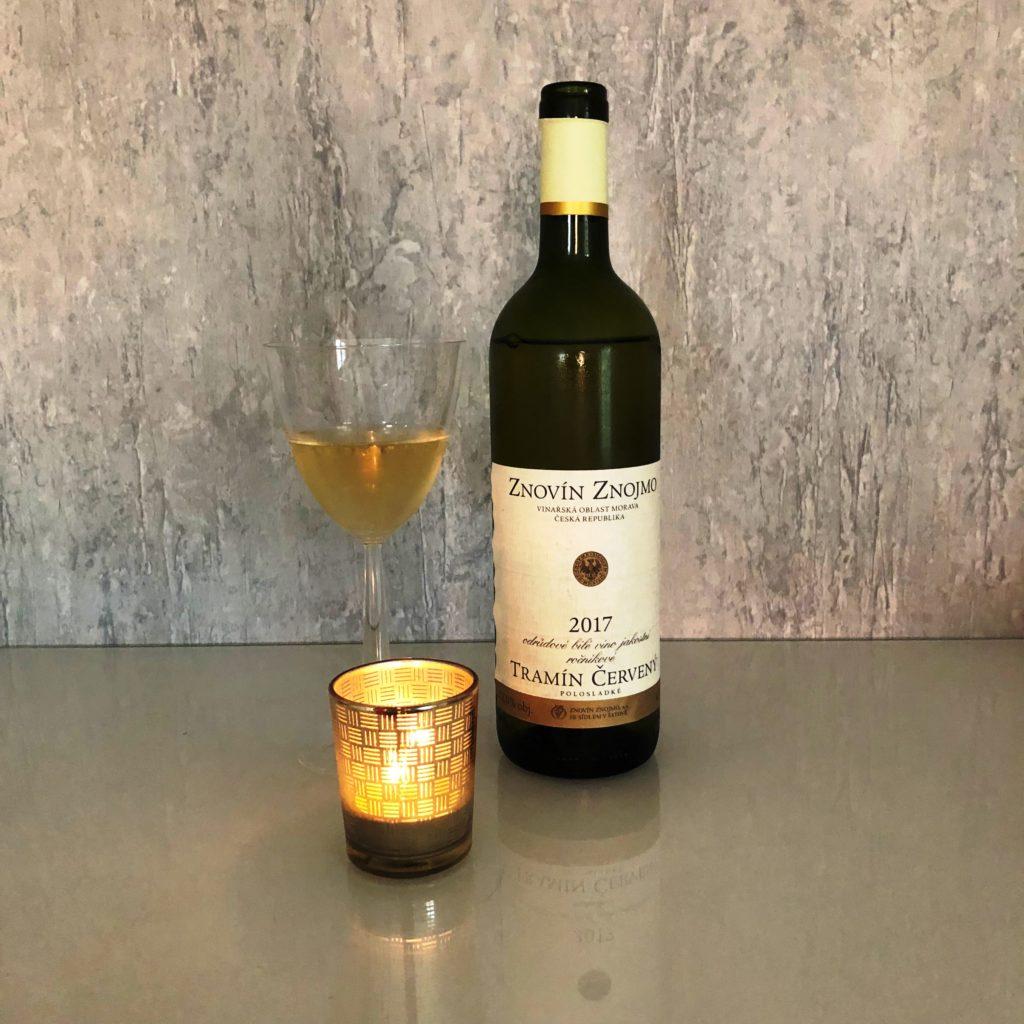 Tramín červený Znovín Znojmo v zelené lahvi, sklenka bílého vína, hořídí svíčka v popředí