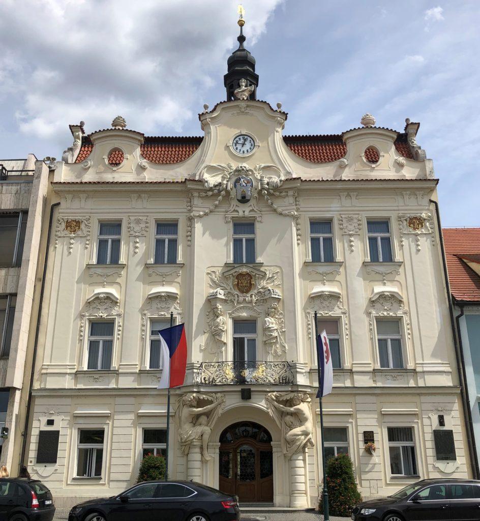 Berounská radnice, náměstí v Berouně, budova se světlou fasádou, českou vlajkou a berounskou vlajkou