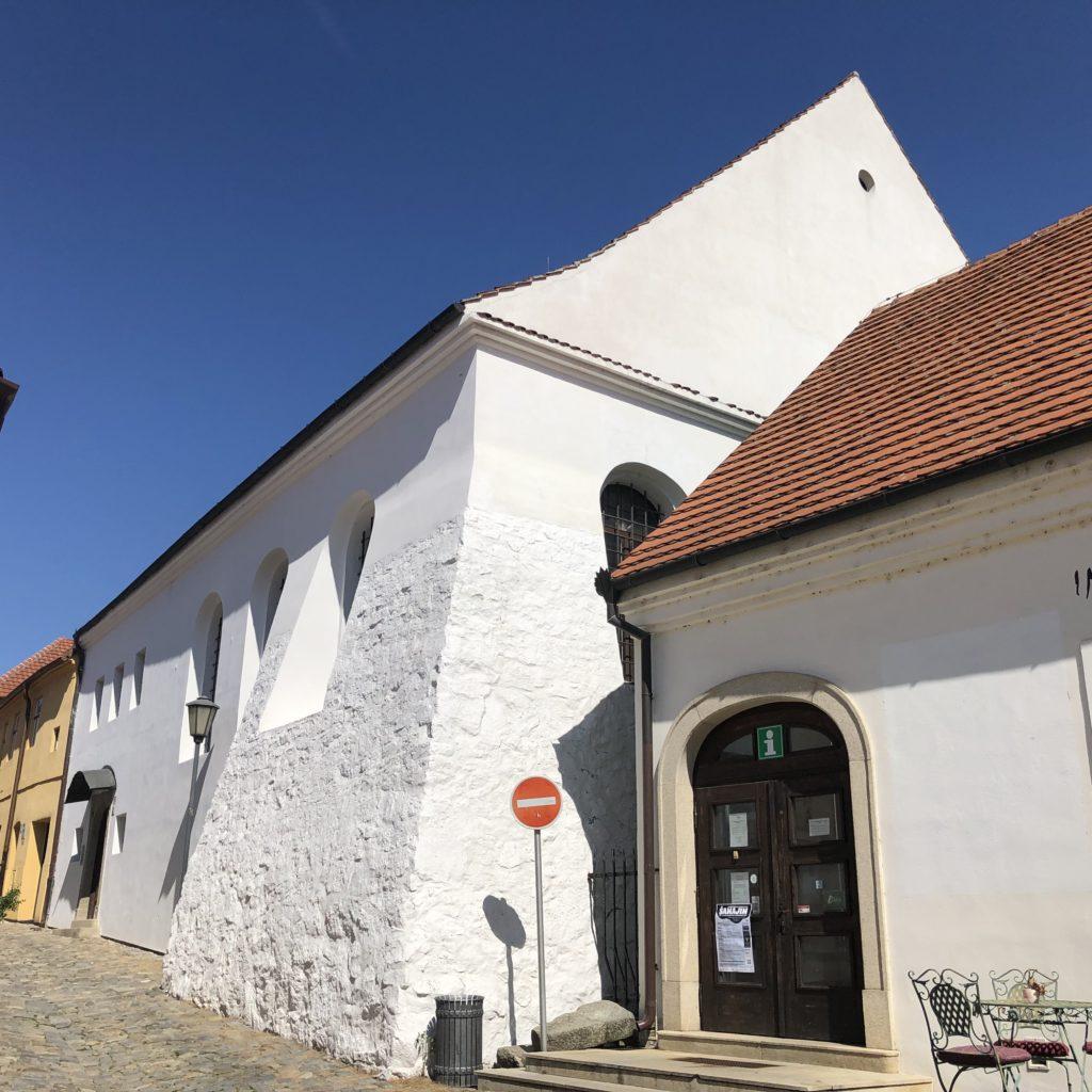 Zadní synagoga v Třebíči v židovské čtvrti zařazené na seznam památek světového kulturního a přírodního dědictví UNESCO, bílá synagoga s červenou střechou osvícená sluncem, modrá obloha