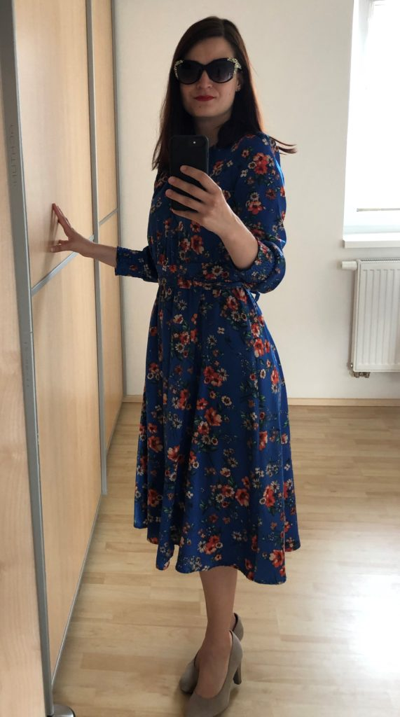 žena s červenou rtěnkou ve slunečních brýlích, tmavě modré květované šaty, elegantní styl