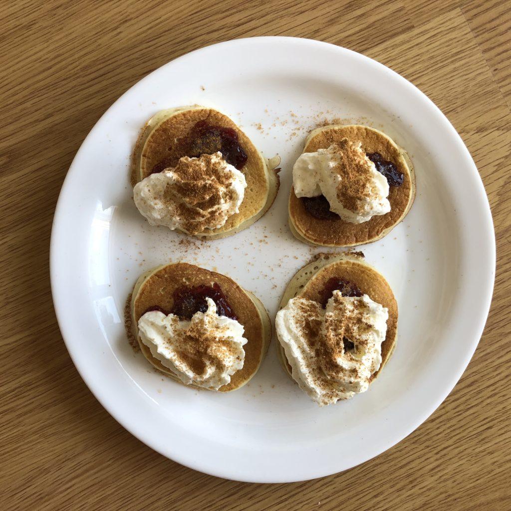 kefírové lívance se šlehačkou, višňovou marmeládou a skořicovým cukrem na bílém talíři na dřevěném podkladu