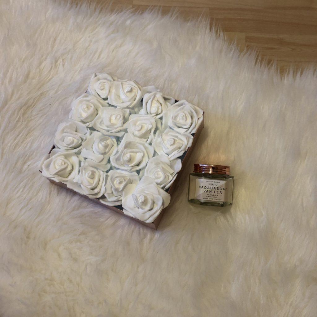 květinová krabička s bílými růžemi v krabičce na bílé ovčí kožešině se svíčkou