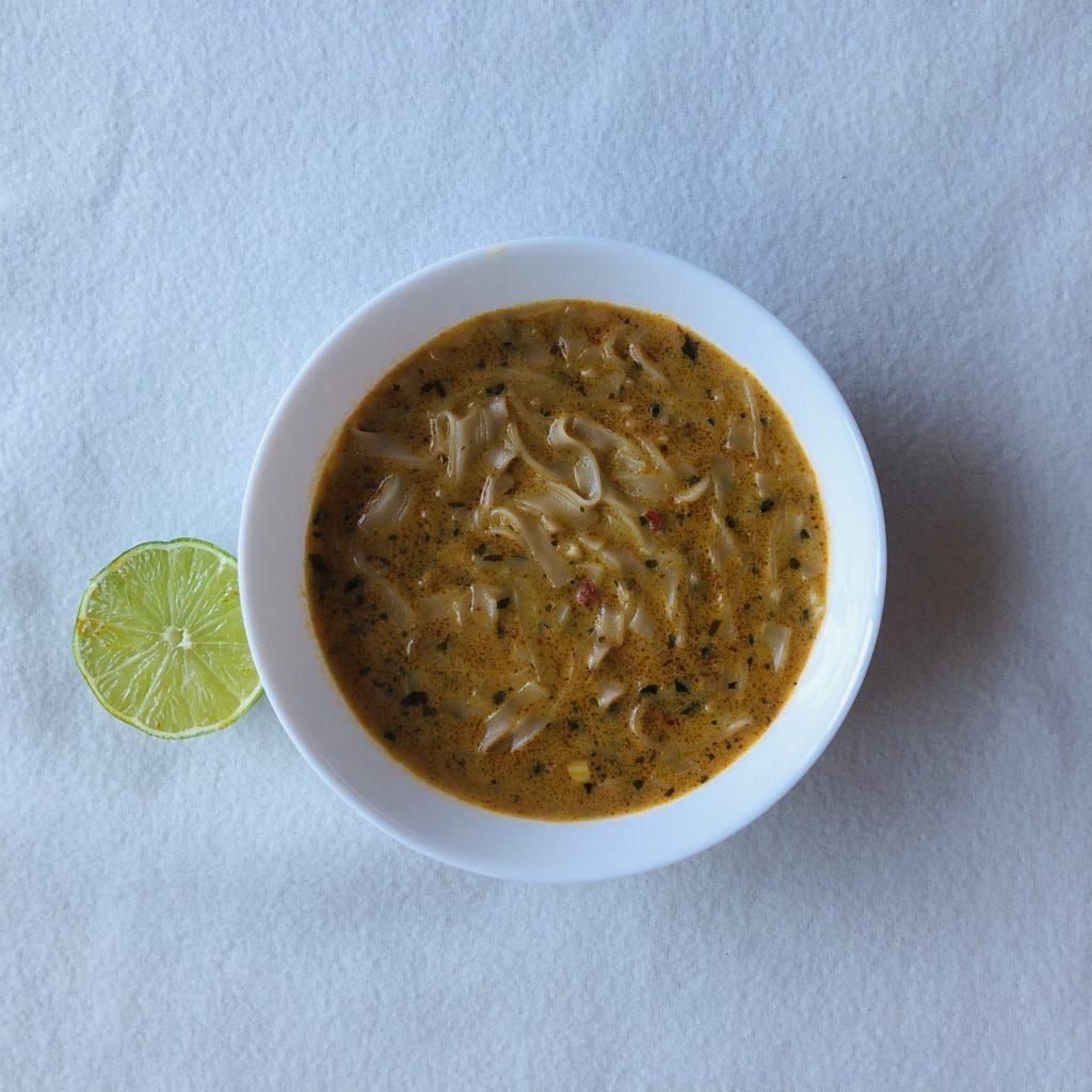 thajská polévka s kokosovým mlékem, nudlemi, červeným kari, v bílé misce s limetkou na bílém pozadí