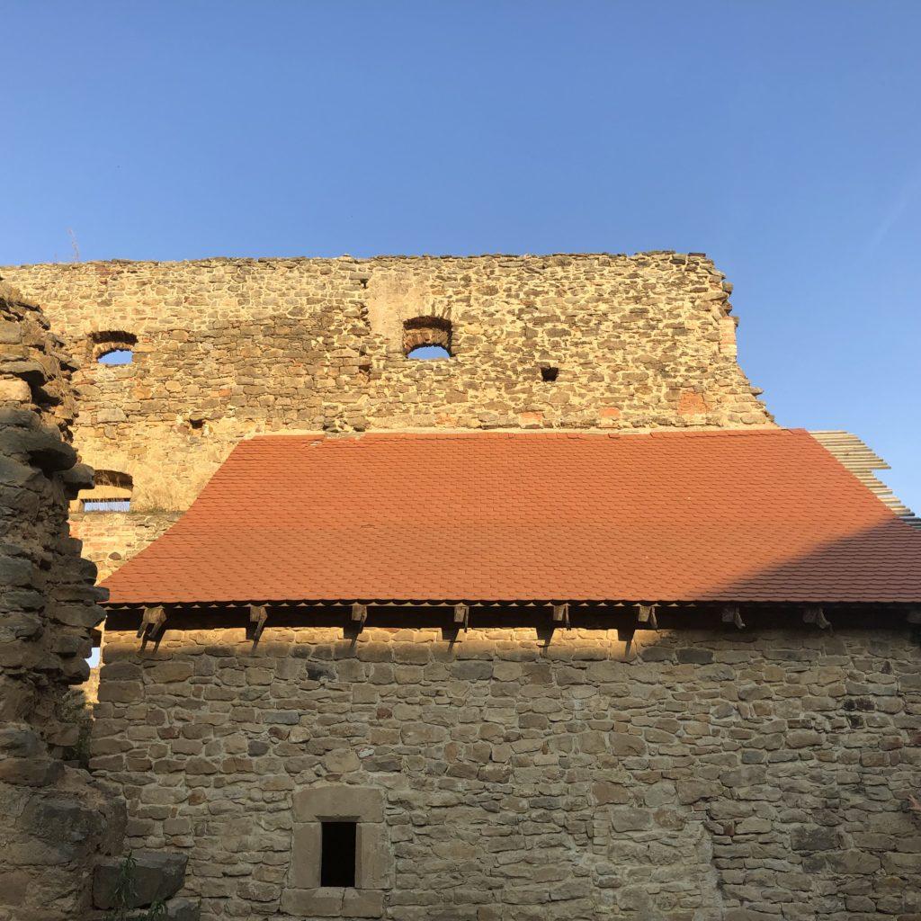 vyšehořovická tvrz, kamenné zdivo, červená střecha z pálených tašek ozářená sluncem, modrá obloha