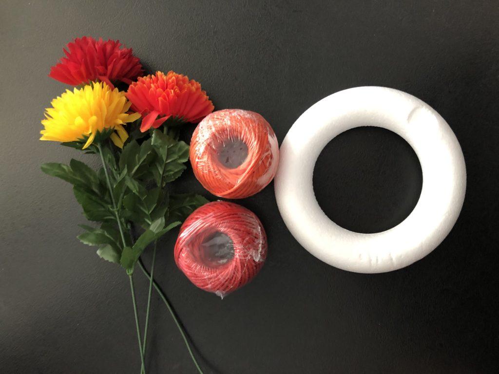 polystyrenový korpus na věnec, klubko s červeným a oranžovým provázkem a umělými květinami v červené, oranžové a žluté barvě.