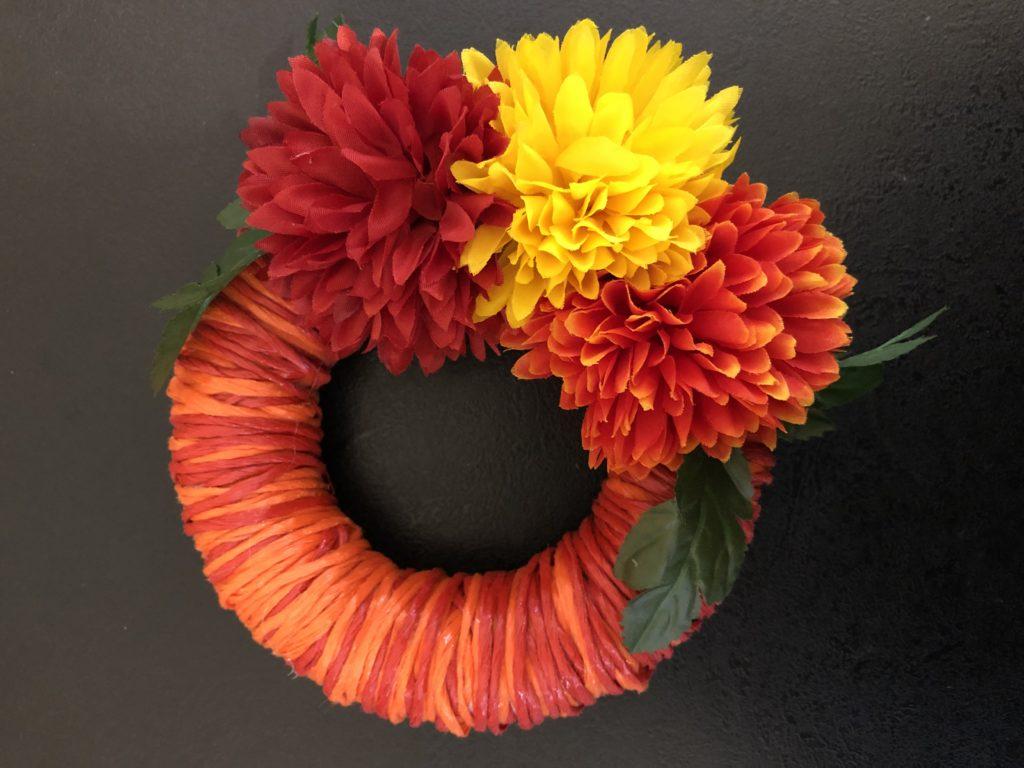 podzimní věnec na dveře v oranžové a červené barvě s umělými květinami v červené, žluté a oranžové.
