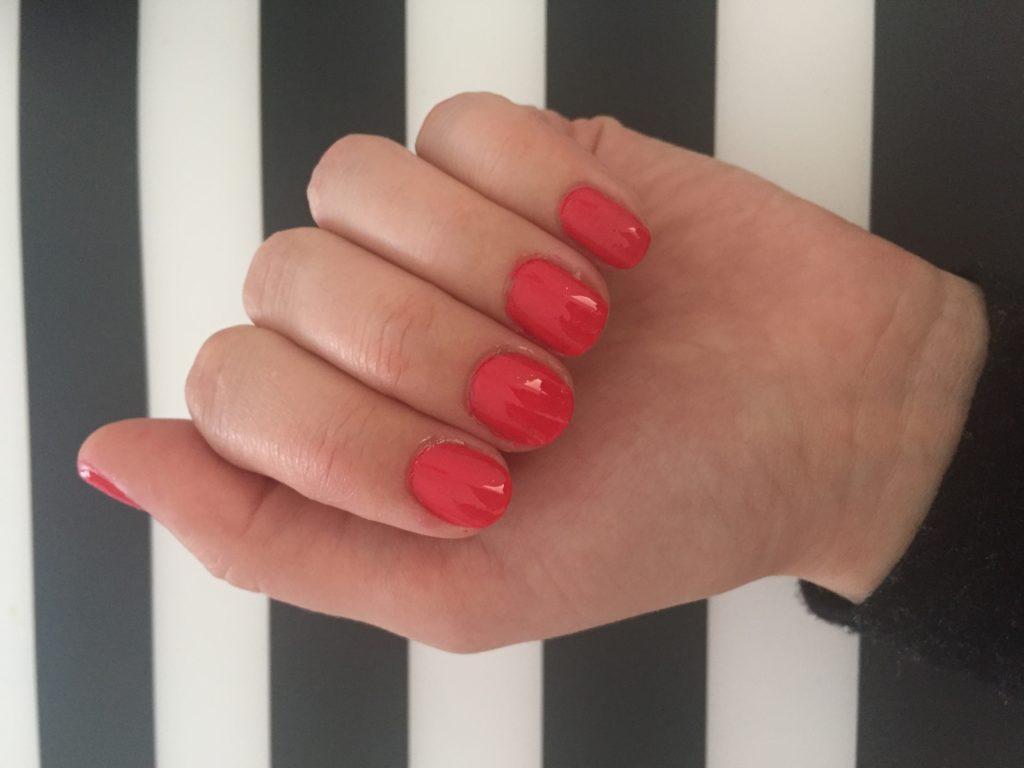 ruka s nehty nalakovanými tmavě růžovým lakem essence legally pink