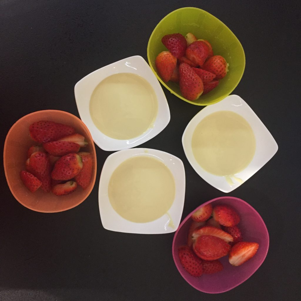 misky s jahodami a misky s rozpuštěnou bílou čokoládou připravené na ovocné fondue, jahody v čokoládě