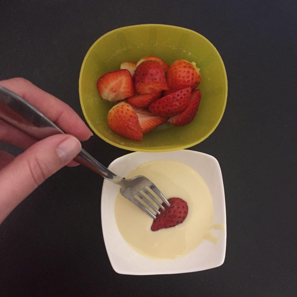 Miska s jahodami, jahoda na vidličce máčená v bílé čokoládě