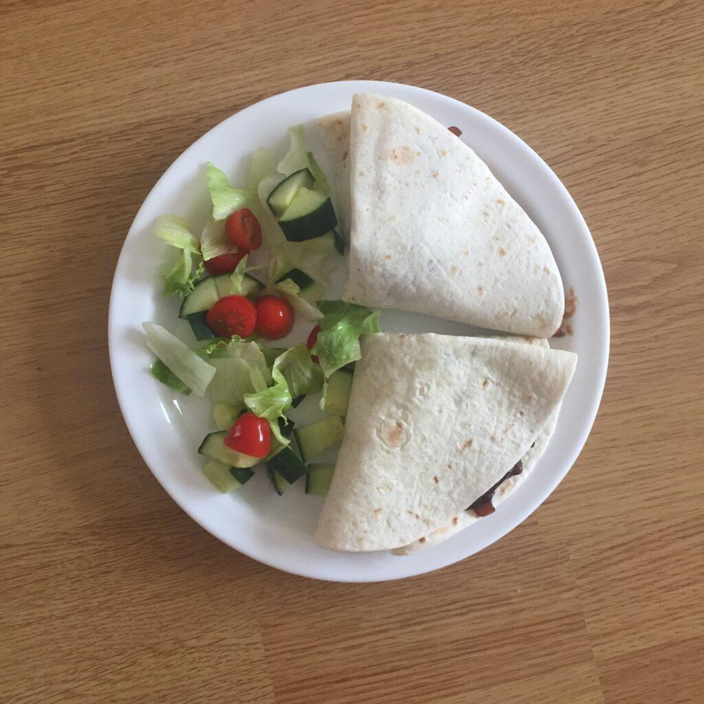 Dvě tortily s trhaným vepřovým masem a karamelizovanou cibulkou, zeleninový salát