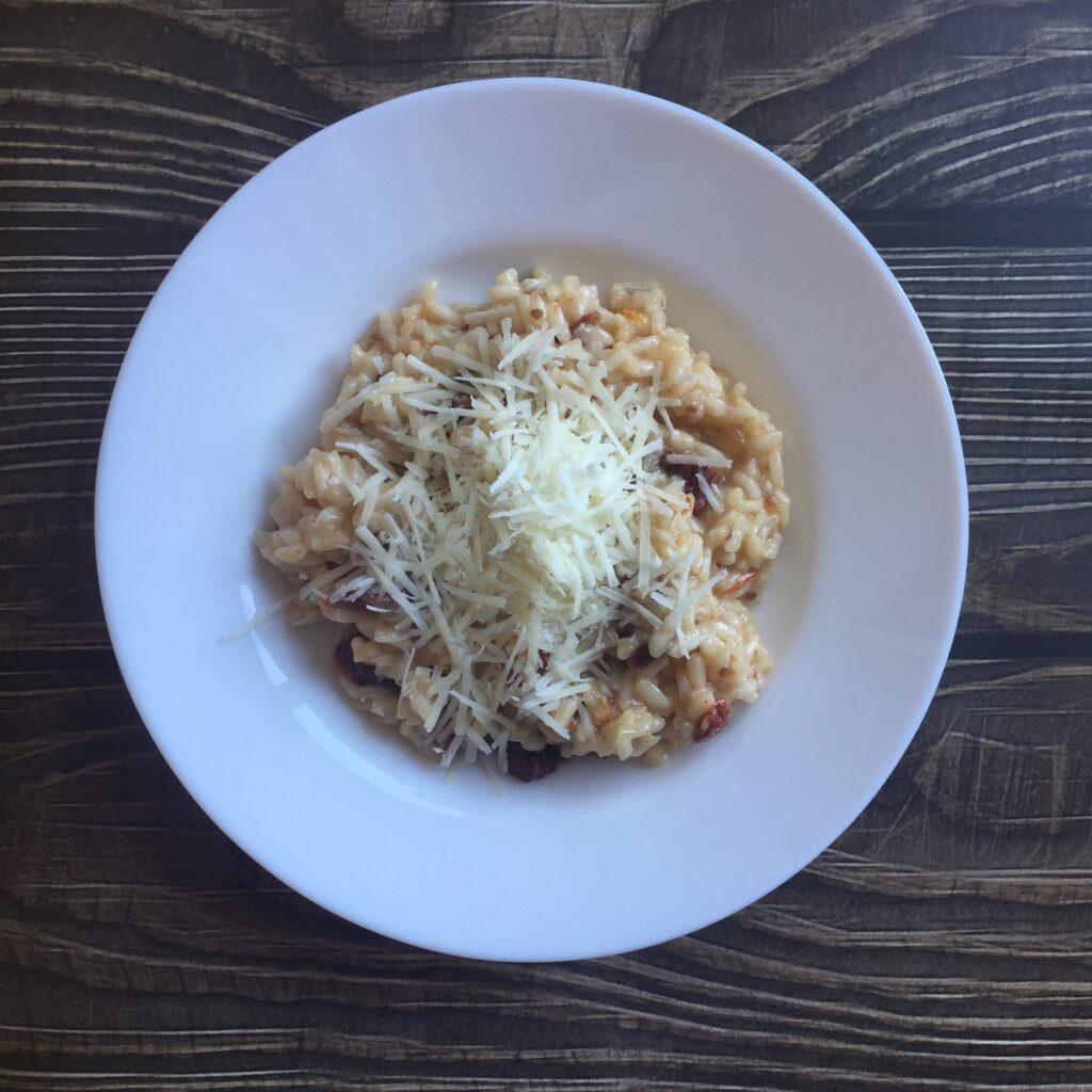 Italské krémové rizoto se sušenými rajčaty posypané sýrem